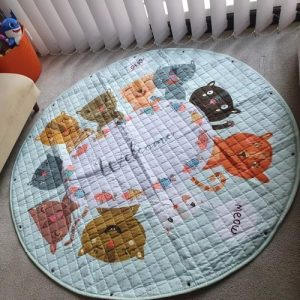 A round children's play mat placed on a carpet. It is white and printed with nine different cat faces with the words 'welcome' and 'meow'.