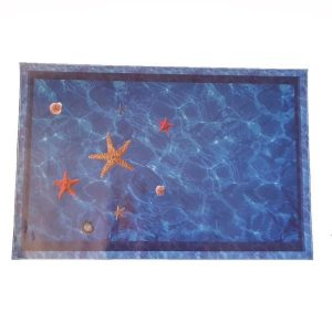 A 3d wall or floor decal of the ocean with star fish and shells.