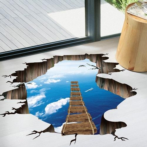 A 3D floor sticker of a broken floor with a ladder. It has a view of clouds and the ocean below.