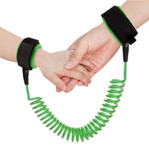 An adults hand is holding a child hands. Both hands are strapped in a green anti-lost wrist link.
