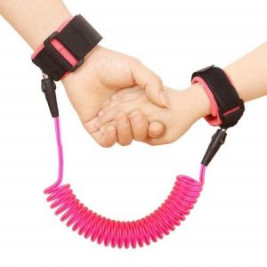 An adults hand is holding a child hands. Both hands are strapped in a pink anti-lost wrist link.