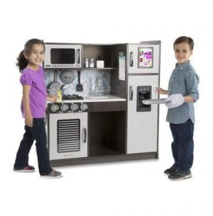 A boy and girl standing in front of their pretend charcoal kitchen by Melissa & Doug. The boy is wearing an oven mitt holding an ice tray.
