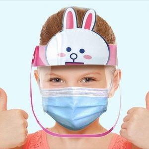 A girl wearing a pink bunny face shield with a blue disposable face mask. Her has both her thumbs up.