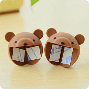 A set of brown teddy corner guards placed on a wooden table. Both are facing the front.