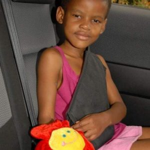 A girl sitting in the backseat of the cat with a secure a kid seatbelt harness. There is a plush yellow and red flower next to her.