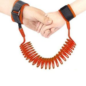 An adults hand is holding a child hands. Both hands are strapped in a orange anti-lost wrist link.